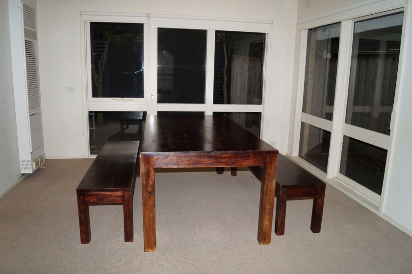 A large, hardwood dining table, complete with benches and big enough for a crowd.