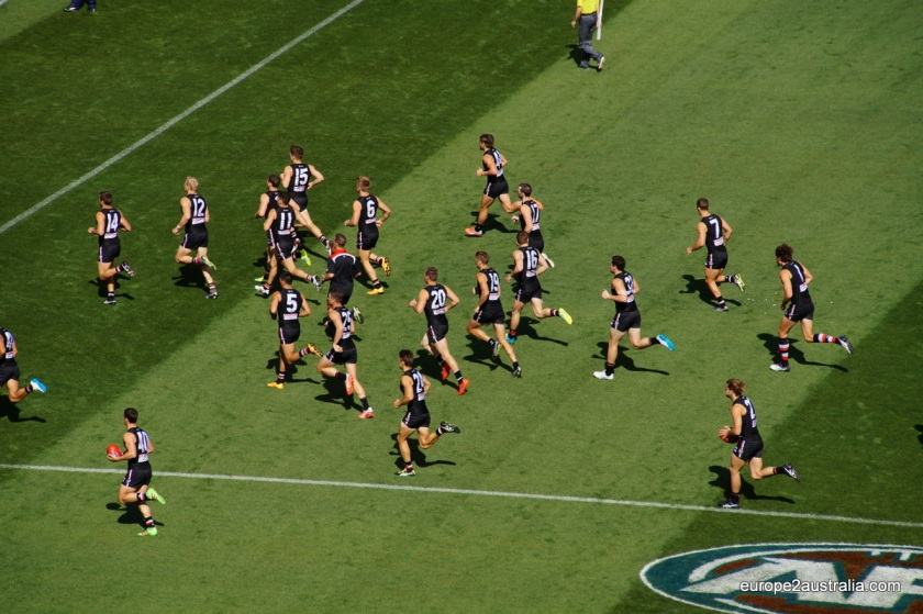 "St. Kilda takes to the field, playing in black as the home team. (For today, the MCG is their ""home"". But this changes.)"