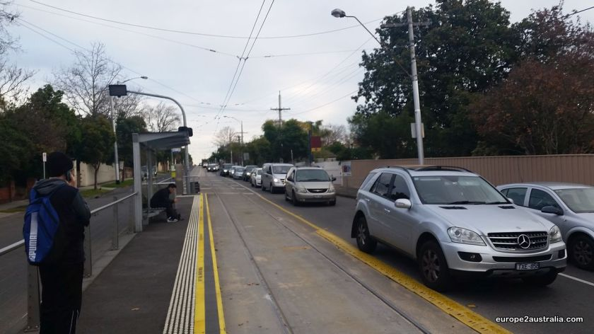 Waiting for the tram, which is sometimes stuck in traffic, as the motorists don't watch out for the tracks.