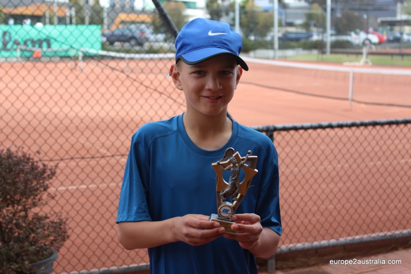 "A happy Kai holding his first ""real"" tennis trophy."